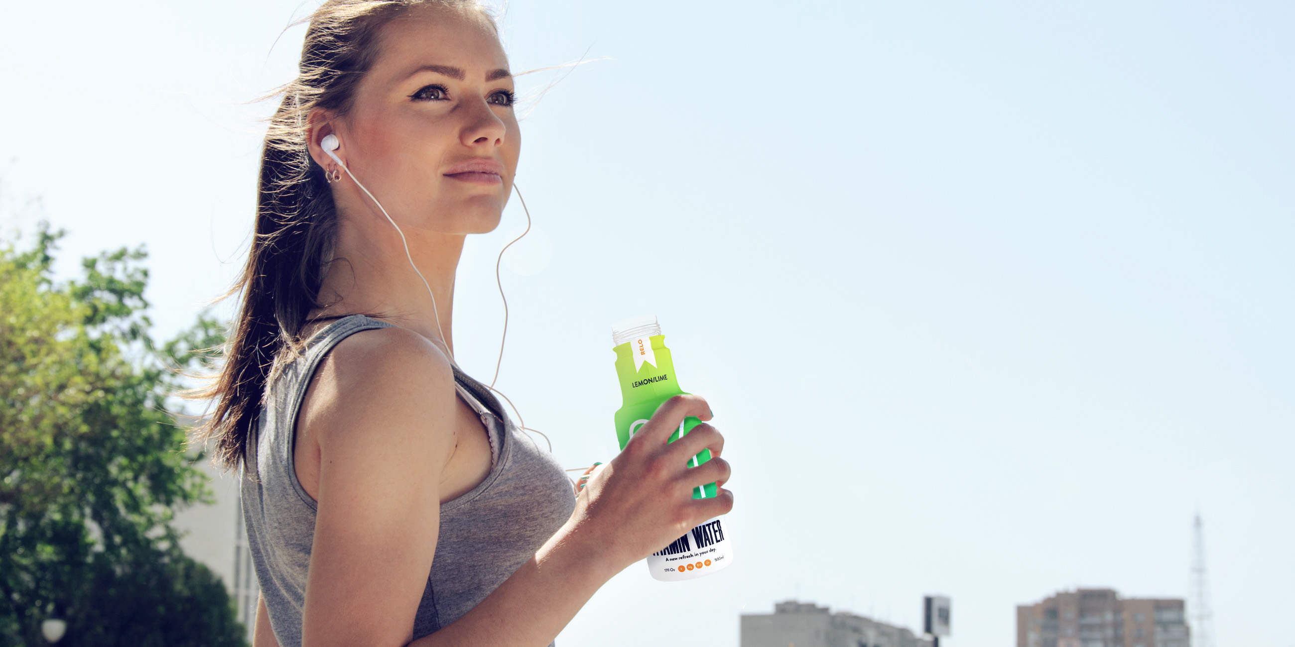 Sport woman drinking water and listening to music